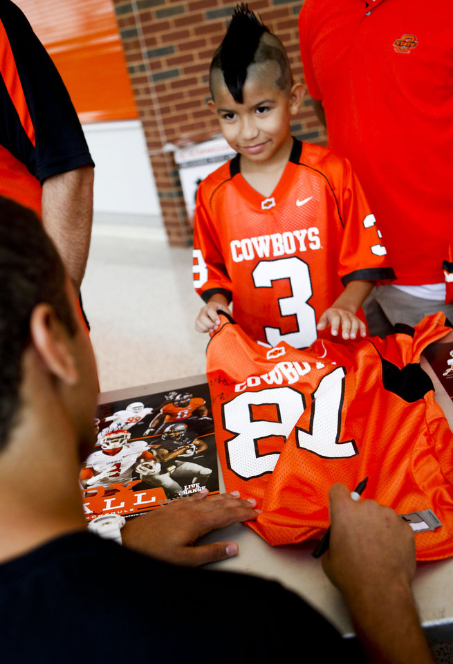Photo - Dominik Villanueva, 9 of Clinton, gets a jersey autographed by Oklahoma State football players August 3, 2013 at Gallagher-Iba Arena for fan appreciation day. Dominik said meeting his favorite player Clint Chelf was