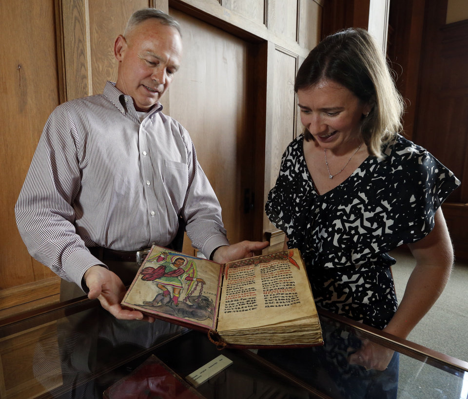 Photo -  John Lovett, director of special collections with the Western History Collection at the University of Oklahoma and Elsbeth Dowd, look at an Abyssinian Bible, part of the George C. McGhee collectiona. Photo by Steve Sisney, The Oklahoman   STEVE SISNEY -