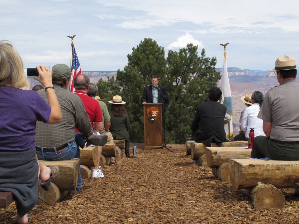 Photo - Glenn Miller, acting administrator for the Federal Aviation Administration's Western-Pacific Region, speaks to a crowd gathered at Grand Canyon National Park, Ariz., about the significance of a 1956 airliner collision over the canyon that killed 128 people, Tuesday, July 8, 2014. The ceremony at the Grand Canyon marked the designation of the crash site as a National Historic Landmark. (AP Photo/Felicia Fonseca)