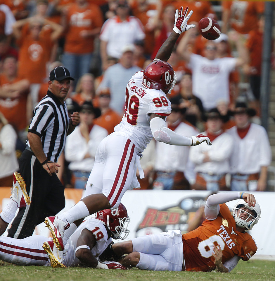 UT's Case McCoy (6) gets a pass off over OU's Chaz Nelson (99) and Eric Striker (19) for a completion during the Red River Rivalry college football game between the University of Oklahoma Sooners (OU) and the University of Texas Longhorns (UT) at the Cotton Bowl Stadium in Dallas, Saturday, Oct. 12, 2013. Photo by Chris Landsberger, The Oklahoman
