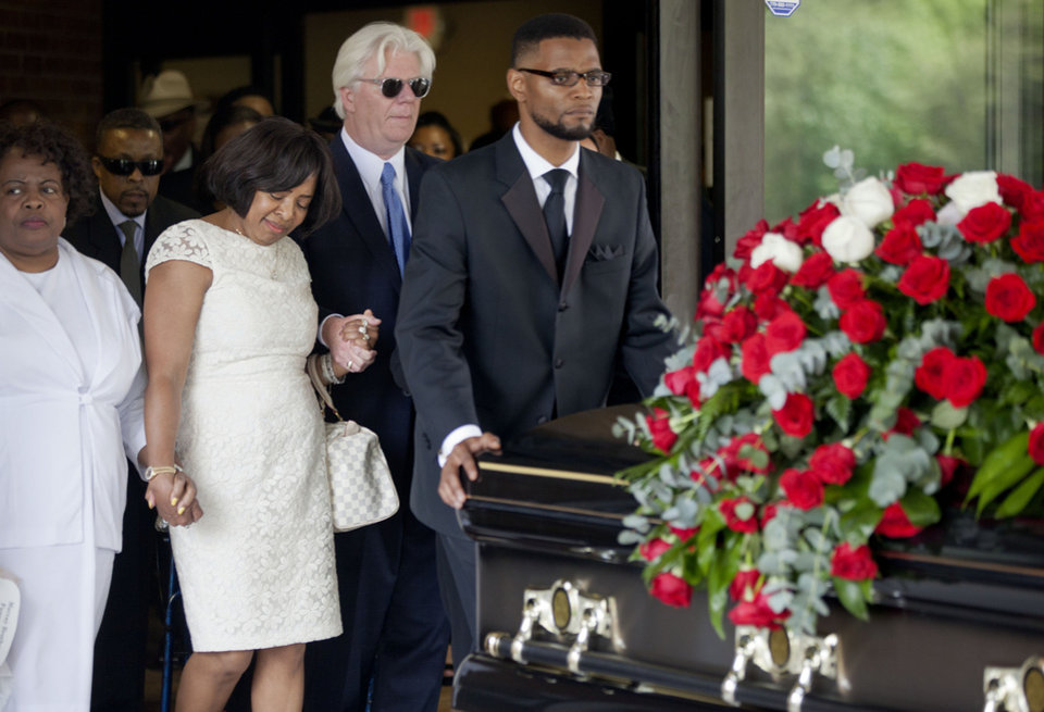 "Donna Kelly Pratte, second from left, the mother of Kris Kross rapper Chris Kelly, follows the casket of her son during his funeral recessional along with her husband James Pratte, second right, Thursday, May 9, 2013, in Atlanta. The 34-year-old Kelly was found dead May 1 of a suspected drug overdose. Kriss Kross was introduced to the music world in 1992 by music producer and rapper Jermaine Dupri after he discovered the pair at a mall in southwest Atlanta. Kelly performed alongside Chris Smith, who known as ""Daddy Mac.""  (AP Photo/David Goldman)"