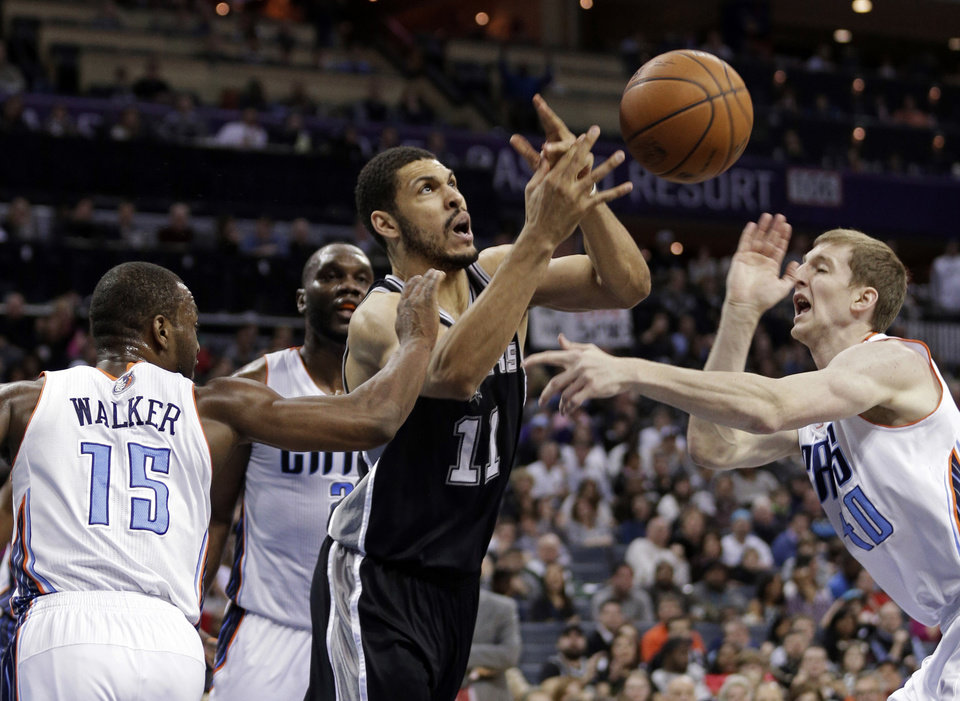 San Antonio Spurs\' Jeff Ayres (11) is fouled as he drives between Charlotte Bobcats\' Kemba Walker (15) and Cody Zeller (40) during the first half of an NBA basketball game in Charlotte, N.C., Saturday, Feb. 8, 2014. (AP Photo/Chuck Burton)