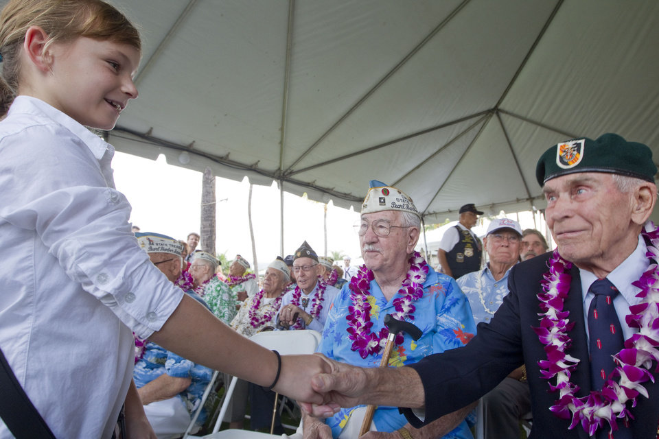 Photo - Gabi Shultz, 10, resident of Joint Base Pearl Harbor Hickam, meets Pearl Harbor survivor Sam Clower, center, of Sacramento, Calif. and Ab Brum, right, retired United States Army Special Forces, of Kaneohe, Hawaii, Friday, Dec. 7, 2012, at Pearl Harbor. Many of the Pearl Harbor Veterans gathered at the World War II Valor In The Pacific National Monument remembering the 71th anniversary of the Dec. 7, 194 Japanese surprise attack on Pearl Harbor in Honolulu. (AP Photo/Eugene Tanner)