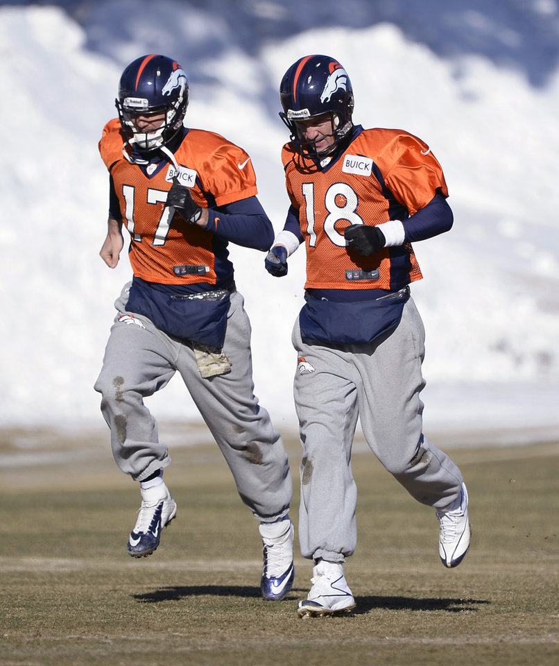 Photo - Denver Broncos quarterback Peyton Manning (18) and Denver Broncos quarterback Brock Osweiler (17) head to drills  during practice at Dove Valley as they prepare for an NFL football game against the San Diego Chargers in the Divisional Round of the Playoffs on Jan. 6, 2014, in Englewood, Colo.  (AP Photo/The Denver Post, John Leyba) MAGS OUT; TV OUT; INTERNET OUT; NO SALES; NEW YORK POST OUT; NEW YORK DAILY NEWS OUT