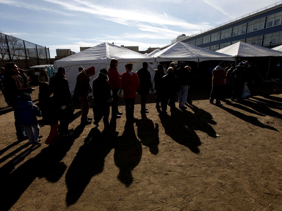 Voters wait in line to cast their ballots under a tent at a consolidated polling station for residents of the Rockaways on Election Day, Tuesday, Nov. 6, 2012, in the Queens borough of New York.  Voting in a the U.S. presidential election was the latest challenge for the hundreds of thousands of people in the New York-New Jersey area still affected by Superstorm Sandy, as they struggled to get to non-damaged polling places to cast their ballots in one of the tightest elections in recent history. (AP Photo/Jason DeCrow) ORG XMIT: NYJD107