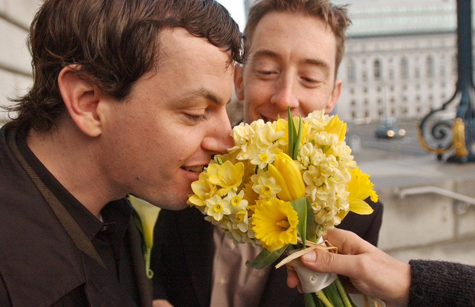 Photo - In this file photo from Tuesday, Feb. 24, 2004, Aaron Carruthers, left, and Keith Haberstuck, of Sacramento, Calif., smell flowers prior to their planned wedding at City Hall in San Francisco. The U.S. Supreme Court decided Friday, Dec. 7, 2012, to hear the appeal of a ruling that struck down Proposition 8, the state's measure that banned same sex marriages. The highly anticipated decision by the court means same-sex marriages will not resume in California any time soon. The justices likely will not issue a ruling until spring of next year. A federal appeals court ruled in February that Proposition 8's ban on same-sex marriage was unconstitutional. But the court delayed implementing the order until same-sex marriage opponents proponents could ask the U.S. Supreme Court to review the ruling. (AP Photo/Ben Margot)