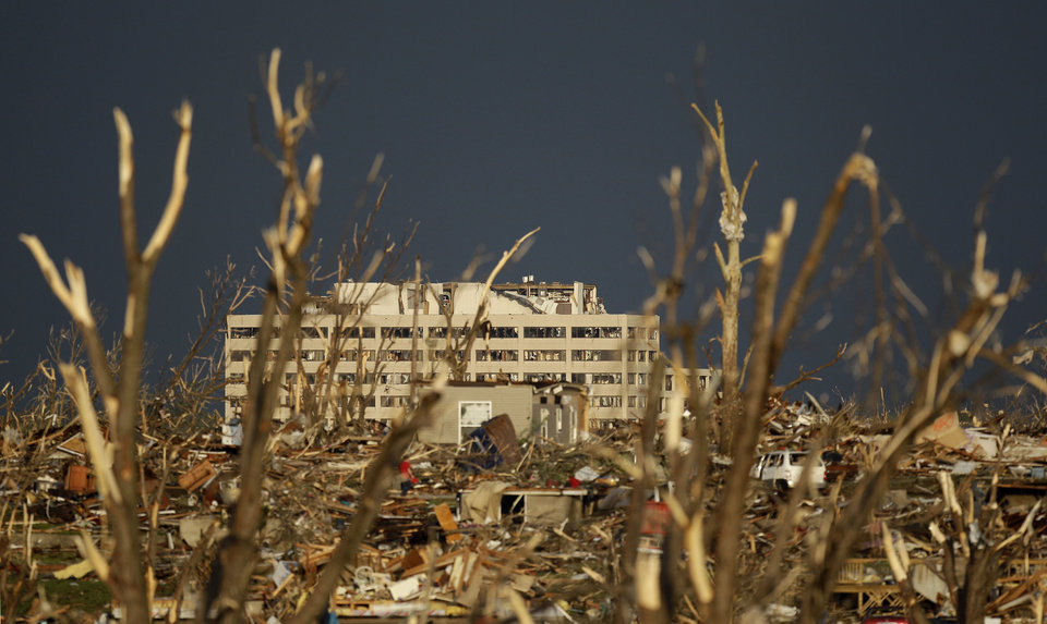 Photo - The damaged St. John's Regional Medical Center is seen in the distance through tornado debris in Joplin, Mo., Monday, May 23, 2011. A large tornado moved through much of the city Sunday, damaging the hospital and hundreds of homes and businesses and killing at least 89 people. (AP Photo/Charlie Riedel) ORG XMIT: MOCR210