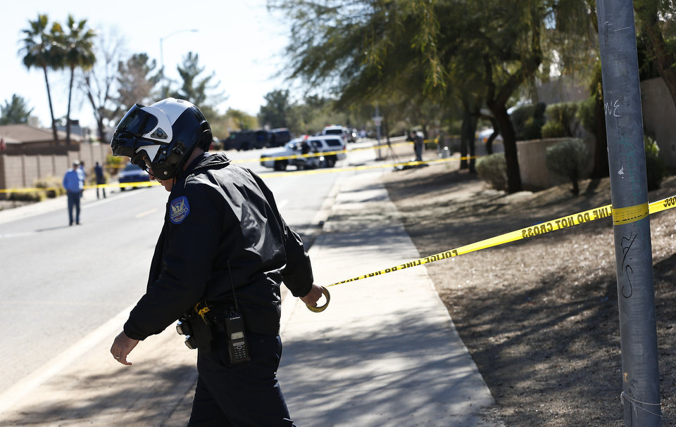 Photo - A Phoenix Police Department officer, puts up police tape near a home of a suspected gunman who opened fire at a Phoenix office building on, wounding three people, one of them critically, and setting off a manhunt that led police to surround his house for several hours before they discovered he wasn't there, Wednesday, Jan. 30, 2013, in Phoenix. Authorities believe there was only one shooter, but have not identified him or a possible motive for the shooting. They don't believe the midmorning shooting at the complex was a random act. (AP Photo/Ross D. Franklin)
