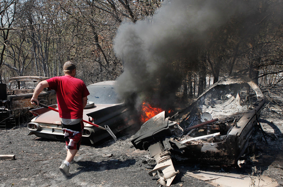 Photo - C. J. Clark runs after grabbing a rake  to a 1961 Fleetwood Cadillac after the front seat burst into flames on the property of Lori Turner at 6000 NE 63 Wednesday; Clark had arrived at Turner's property to help her with clean up when her home and vehicles were burned yesterday when wildfires ravaged land and property that stretched from NE 50 on the south to Hefner Road on the north.  The fire extended from Sooner Road to Midwest Blvd.  Clark is a longtime friend of Turner's family.   Photo taken Wednesday, Aug. 31, 2011. Photo by Jim Beckel, The Oklahoman