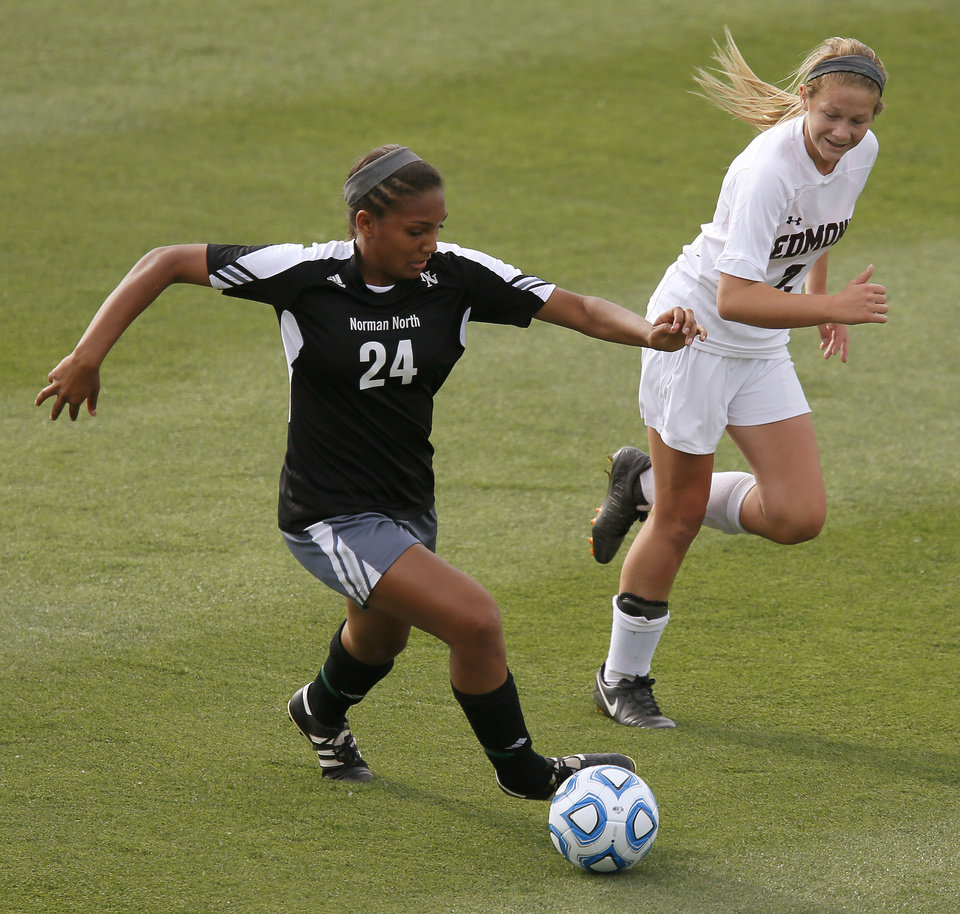 Photo - Norman North's Yazmeen Ryan goes past Edmond Memorial's Hannah Molone during the Class 6A girls soccer championship between Edmond Memorial and Norman North in Norman, Okla., Friday, May 16, 2014. Photo by Bryan Terry, The Oklahoman