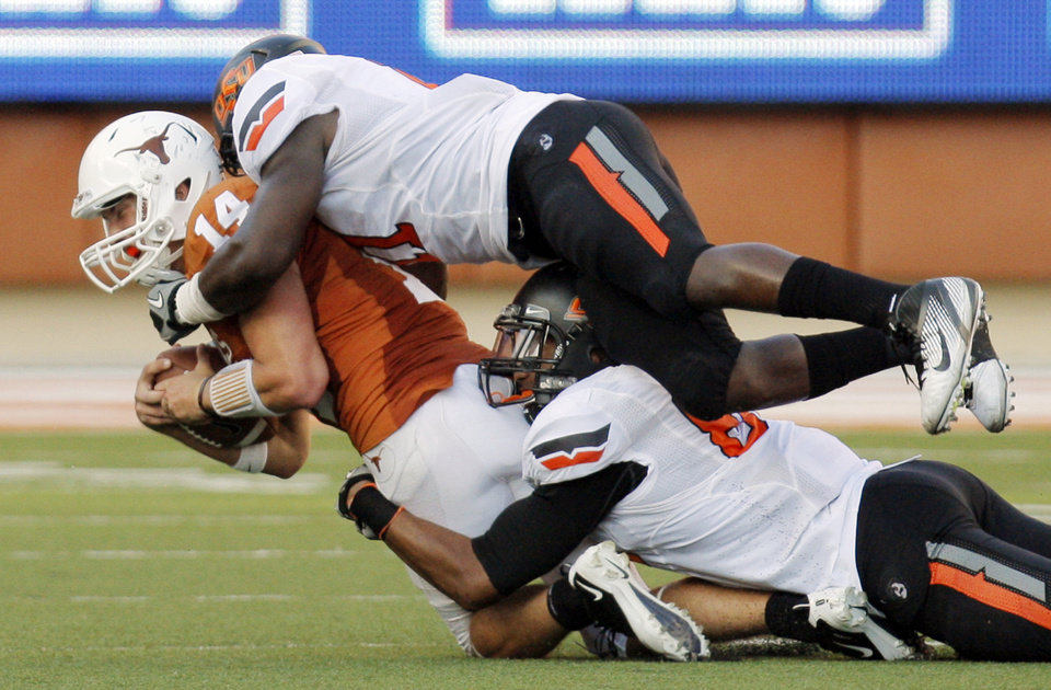 Oklahoma State\'s Shaun Lewis (11), top, and Wilson Youman (86) bring down Texas\' David Ash (14) in the second half during a college football game between the Oklahoma State University Cowboys (OSU) and the University of Texas Longhorns (UT) at Darrell K Royal-Texas Memorial Stadium in Austin, Texas, Saturday, Oct. 15, 2011. OSU won, 38-26. Photo by Nate Billings, The Oklahoman