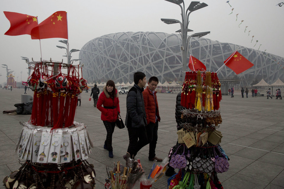 Photo - In this picture taken, Sunday, Feb. 23, 2014, tourists pass by memorabilia on sale near the iconic Bird's Nest National Stadium in Beijing, China. The National Stadium, nicknamed the Bird's Nest because of its lattice design, has become a key Beijing landmark and a favored backdrop for visitors' snapshots. But few tourists are willing to pay more than $8 to tour the facility as enthusiasm for the 2008 Games fades, and the venue has struggled to fill its space with events. Beijing, which spent more than $2 billion to build 31 venues for the 2008 Summer Games, is reaping some income and tourism benefits from two flagship venues, though many sites need government subsidies to meet hefty operation and maintenance costs. (AP Photo/Ng Han Guan)