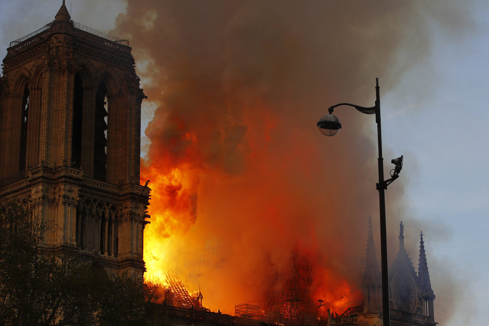 Photo - Notre Dame cathedral is burning in Paris, Monday, April 15, 2019. A catastrophic fire engulfed the upper reaches of Paris' soaring Notre Dame Cathedral as it was undergoing renovations Monday, threatening one of the greatest architectural treasures of the Western world as tourists and Parisians looked on aghast from the streets below. (AP Photo/Francois Mori)