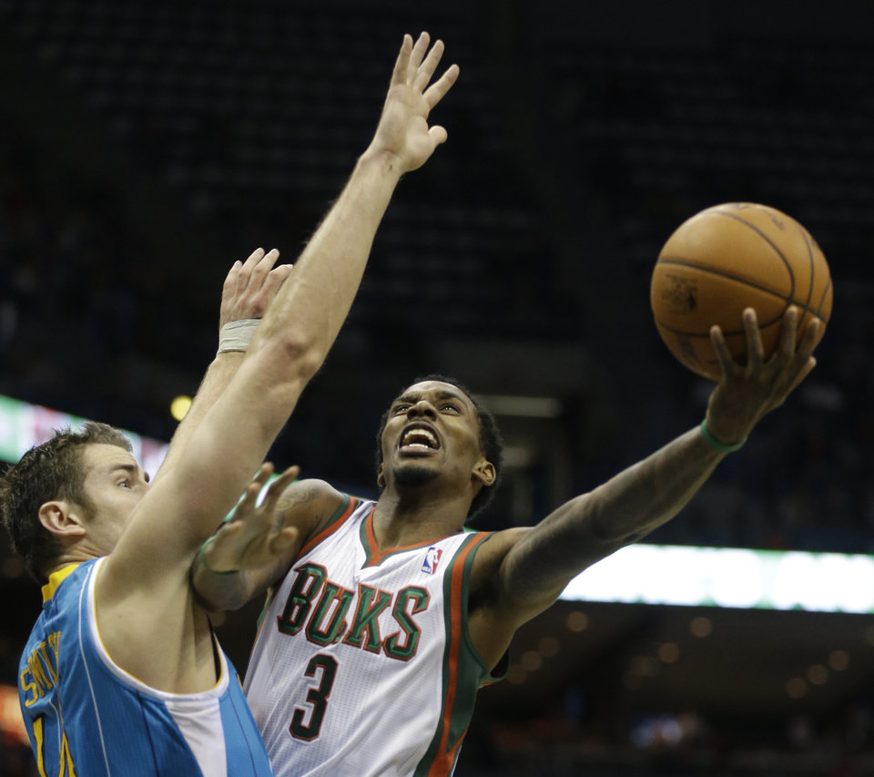 Photo -   Milwaukee Bucks' Brandon Jennings drives to the basket against New Orleans Hornets' Jason Smith, left, during the second half of an NBA basketball game Saturday, Nov. 17, 2012, in Milwaukee. (AP Photo/Jeffrey Phelps)