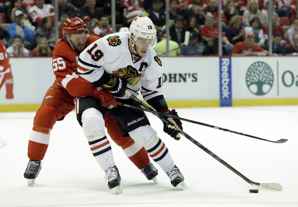 Photo - Detroit Red Wings defenseman Niklas Kronwall (55), of Sweden, defends Chicago Blackhawks center Jonathan Toews (19) during the first period in Game 4 of the Western Conference semifinals in the NHL hockey Stanley Cup playoffs series in Detroit, Thursday, May 23, 2013. (AP Photo/Paul Sancya)