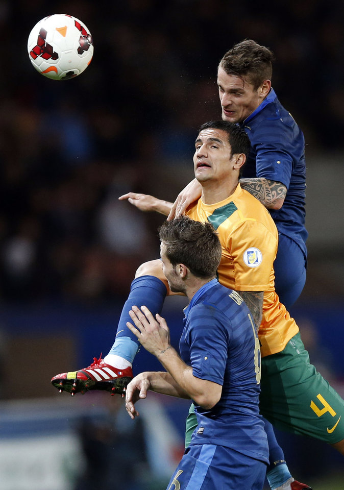 Photo - France's Mathieu Debuchy, top, challenges  to head the ball with Australia's Tim Cahill, center, as France's Yohan Cabaye, bottom, looks on, during their international soccer friendly match between France and Australia at the Parc Des Princes stadium in Paris, France, Friday, Oct.11,2013. (AP Photo/Francois Mori)
