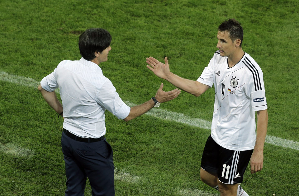Germany's Miroslav Klose, right, is congratuled by head coach Joachim Loew after being substituted during the Euro 2012 soccer championship quarterfinal match between Germany and Greece in Gdansk, Poland, Friday, June 22, 2012. (AP Photo/Gero Breloer)