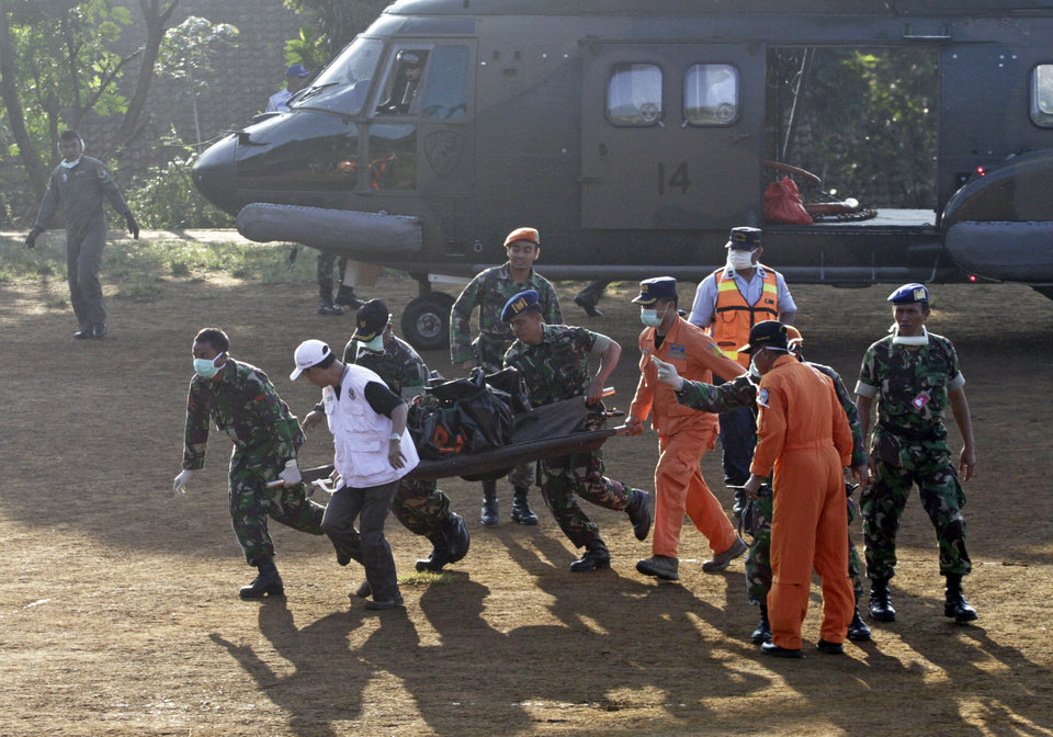 Photo -   Indonesian soldiers carry a victim of Wednesday's plane crash at Cijeruk in Bogor, West Java, Indonesia, Saturday, May 12, 2012. Search teams who scaled a volcano's steep slopes found at least 12 bodies Friday near the wreckage of the Russian-made Sukhoi Superjet-100 that crashed in Indonesia during a demonstration flight for potential buyers, an official said. All 45 aboard the jetliner that crashed Wednesday are feared dead.(AP Photo/Achmad Ibrahim)