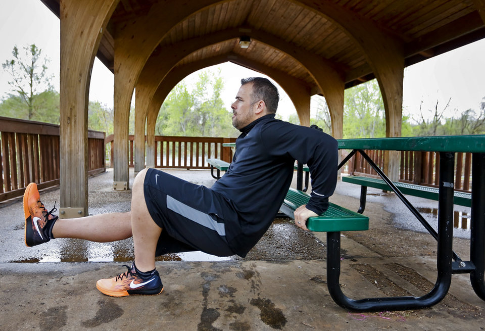 Photo - David Brown exercises at Hafer Park on Monday, April 21, 2014, in Edmond, Okla. as he prepares to run his first half marathon in this weekend's Memorial Marathon that will allow him to complete what he calls a