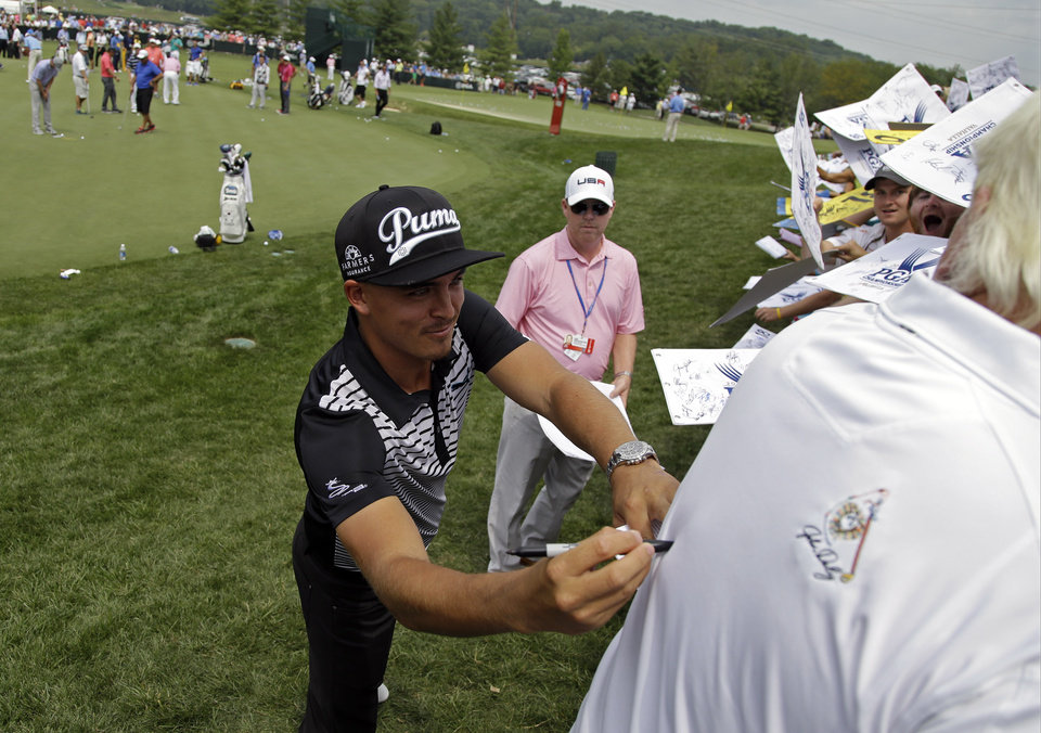Photo - Rickie Fowler, left, pretends to sign autograph on the back of John Daly before a practice round for the PGA Championship golf tournament at Valhalla Golf Club on Wednesday, Aug. 6, 2014, in Louisville, Ky. The tournament is set to begin on Thursday. (AP Photo/John Locher)
