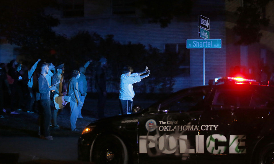 Photo - Protesters raise their hands in front of the Oklahoma City Police Department as a tear gas cloud goes in the air in Oklahoma City, Saturday, May 30, 2020. The protest was in response to the death of George Floyd. [Sarah Phipps/The Oklahoman]