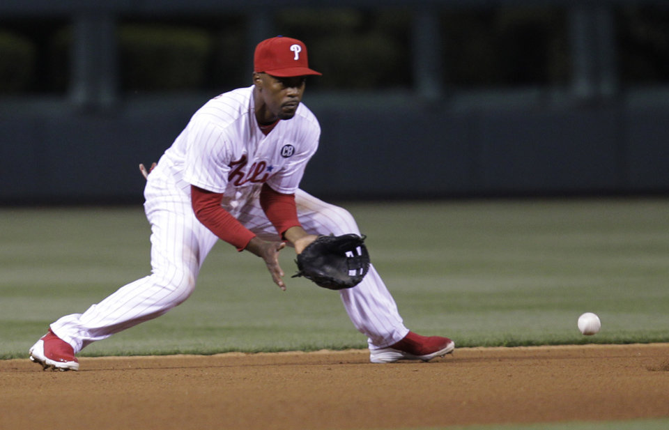 Photo - Philadelphia Phillies' Jimmy Rollins fields a ground ball hit by Washington Nationals' Danny Espinosa and throws to second to get out Nationals' Jayson Werth in the fourth inning of a baseball game on Friday, May 2, 2014, in Philadelphia. (AP Photo/Laurence Kesterson)