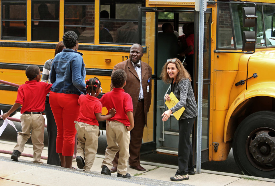 Photo - Ronald E. McNair Discovery Learning Academy staff members help usher students onto their buses Wednesday, Aug. 21, 2013, a day after an armed suspect caused an ordeal at their school in Decatur, Ga. The learning academy held classes at McNair High School on Wednesday after a gunman on Tuesday held one or two staff members captive and fired into the floor of the school office. As officers swarmed the campus outside, he shot at them at least a half a dozen times with an assault rifle from inside the school and they returned fire, police said. (AP Photo/Atlanta Journal-Constitution, Jason Getz)