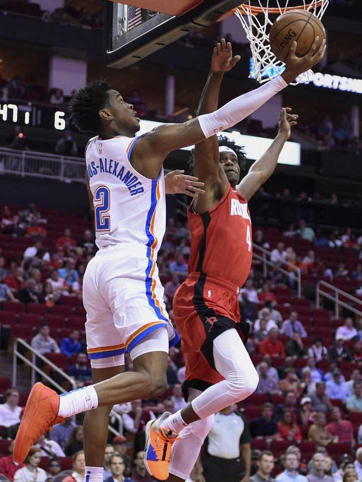 Photo - Oklahoma City Thunder guard Shai Gilgeous-Alexander (2) shoots as Houston Rockets forward Danuel House Jr. defends during the first half of an NBA basketball game, Monday, Oct. 28, 2019, in Houston. (AP Photo/Eric Christian Smith)