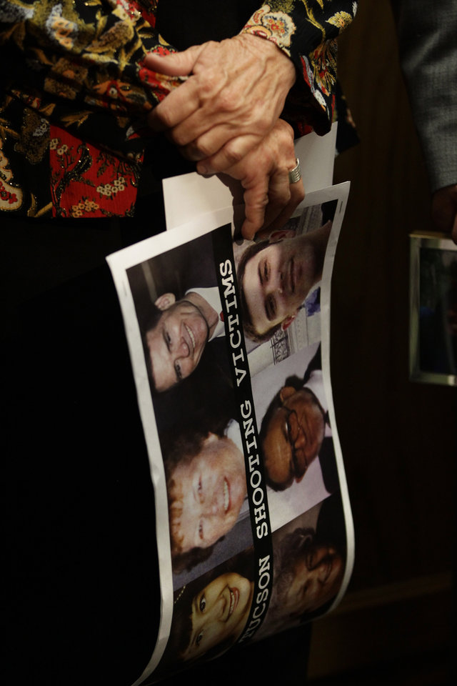 A participant  in a news conference in favor of proposed gun control legislation holds a poster picturing victims from the Tucson shooting, inside the Colorado State Capitol, in Denver, Monday March 4, 2013. State Senate committees began work Monday on a package of gun-control measures that already have cleared the House which include limits on ammunition magazine sizes and expanded background checks to include private sales and online purchases. (AP Photo/Brennan Linsley)