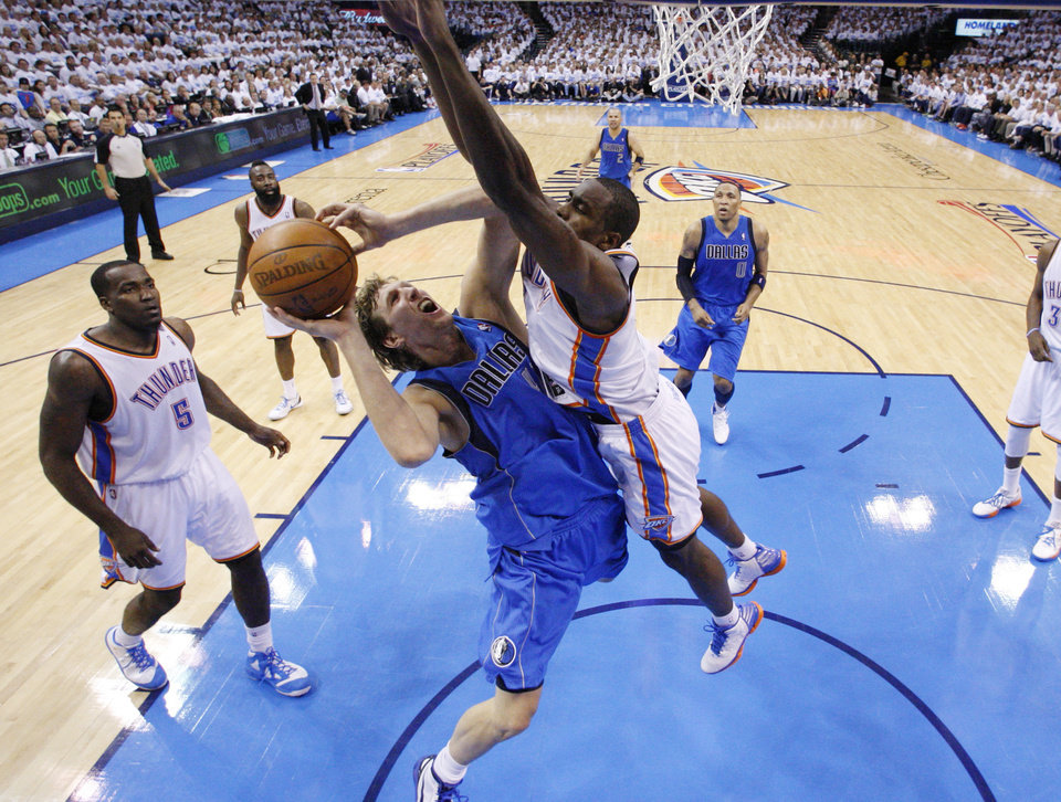 Photo -   Dallas Mavericksforward Dirk Nowitzki, center, shoots as Oklahoma City Thunder forward Serge Ibaka , right, defends, in the second quarter of Game 2 in the first round of the NBA basketball playoffs, in Oklahoma City, Monday, April 30, 2012. (AP Photo/Sue Ogrocki)