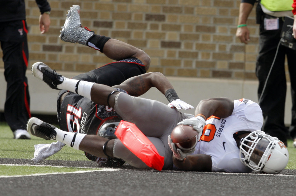 Oklahoma State\'s Herschel Sims (18) dives for the end zone as Texas Tech\'s D.J. Johnson (12) tackles him during a college football game between Texas Tech University (TTU) and Oklahoma State University (OSU) at Jones AT&T Stadium in Lubbock, Texas, Saturday, Nov. 12, 2011. Photo by Sarah Phipps, The Oklahoman ORG XMIT: KOD