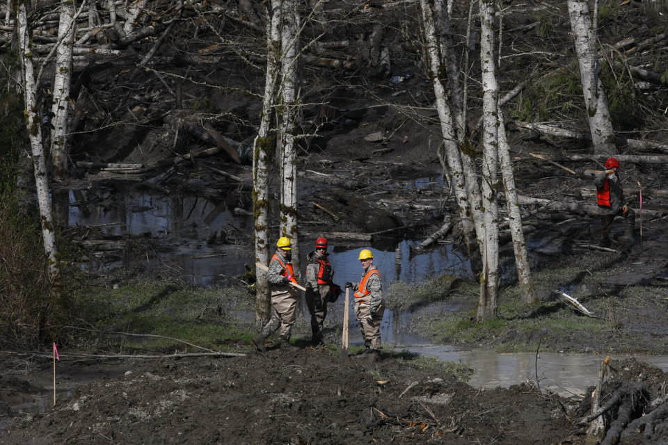 Photo - Workers search for articles and belongings at the scene of the deadly March 22 mudslide, Monday, March 31, 2014, in Oso, Wash. The number of confirmed dead has reached 24. More than two dozen people remain missing, authorities have said. (AP Photo/The Herald, Sofia Jaramillo, Pool)