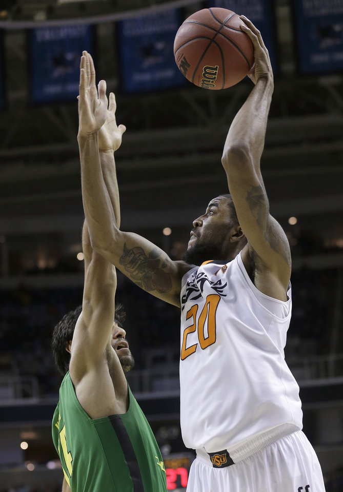 Photo - Oklahoma State forward Michael Cobbins (20) shoots over Oregon forward Arsalan Kazemi (14) during the first half of a second-round game in the NCAA college basketball tournament in San Jose, Calif., Thursday, March 21, 2013. (AP Photo/Jeff Chiu) ORG XMIT: SJA119