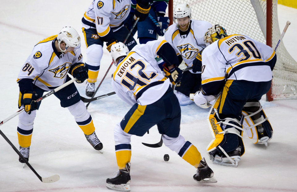 Photo - Nashville Predators' Colton Sissons, from left to right, Mattias Ekholm, of Sweden, Ryan Ellis and goalie Carter Hutton defend against the Vancouver Canucks during the second period of an NHL hockey game Wednesday, March 19, 2014. (AP Photo/The Canadian Press, Darryl Dyck)