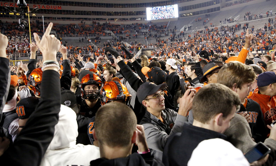 Photo -  Oklahoma State commit Kamryn Farrar was among the fans rushing the field following OSU's upset of West Virginia last week. [PHOTO BY SARAH PHIPPS, THE OKLAHOMAN]