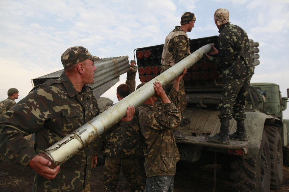 Photo - Ukrainian soldiers load a Grad missile during fighting with pro-Russian separatists close to Luhansk, eastern Ukraine, Monday, Aug. 18, 2014. Dozens of civilians were killed Monday when separatist rebels shelled a convoy of refugees trying to flee war-torn eastern Ukraine, a top Ukrainian official said. A top rebel chief said no such attack had occurred. (AP Photo/Petro Zadorozhnyy)