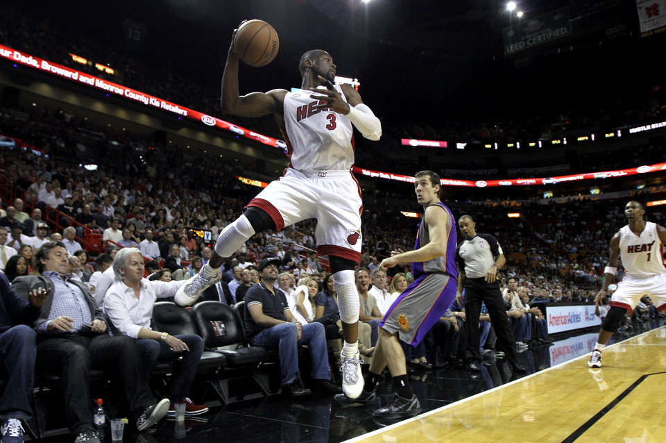 Phoenix Suns\' Goran Draic (1) chases Miami Heat\'s Dwyane Wade (3) as Wade keeps the ball in bounds during the first half of an NBA basketball game in Miami, Monday, Nov. 5, 2012. (AP Photo/J Pat Carter)