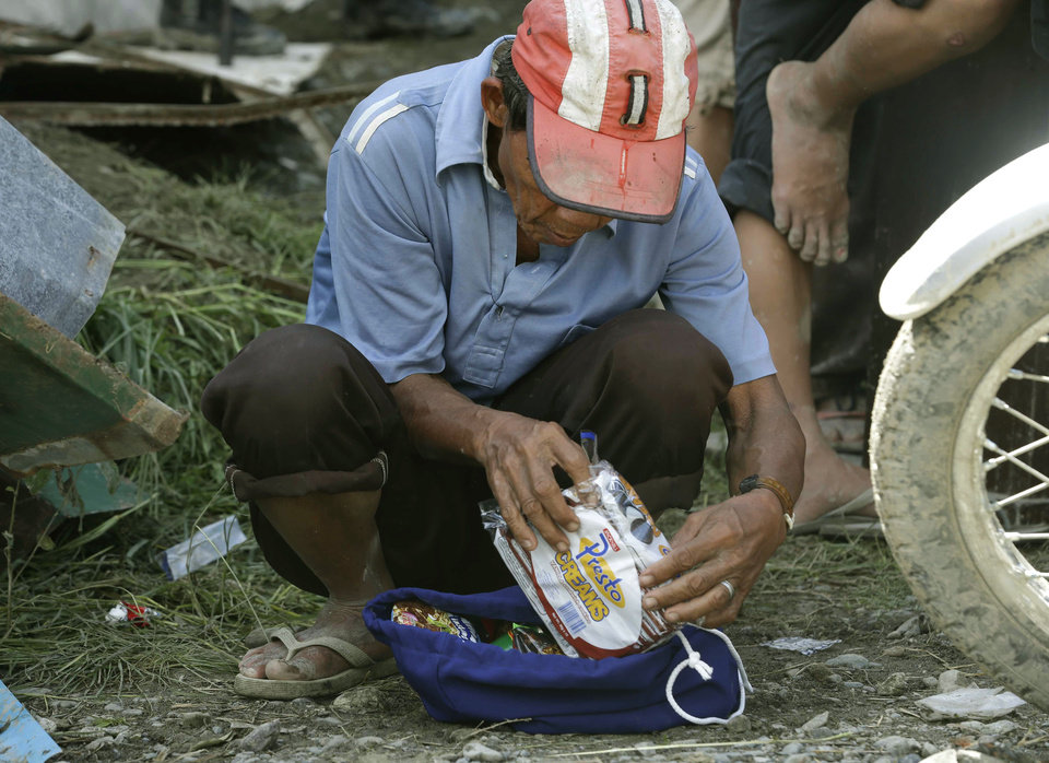A flash flood survivor checks the contents of a bag of food supplies following Tuesday's devastating typhoon, in New Bataan township, Compostela Valley in the southern Philippines, Thursday, Dec. 6, 2012.  The powerful typhoon that washed away emergency shelters, a military camp and possibly entire families in the southern Philippines has killed hundreds of people with nearly 400 missing, authorities said Thursday. (AP Photo/Bullit Marquez)