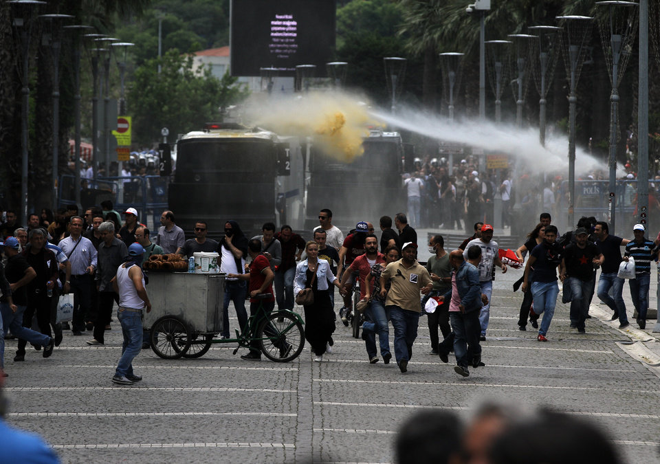 Photo - Police use water cannons and teargas to disperse people gathered to commemorate the Soma mine accident victims and protest the government's labor policy in Izmir, Turkey, late Friday, May 16, 2014. A Turkish mining company defended its safety record Friday, four days after over 250 people died in an underground blaze at its coal mine in western Turkey.(AP Photo)