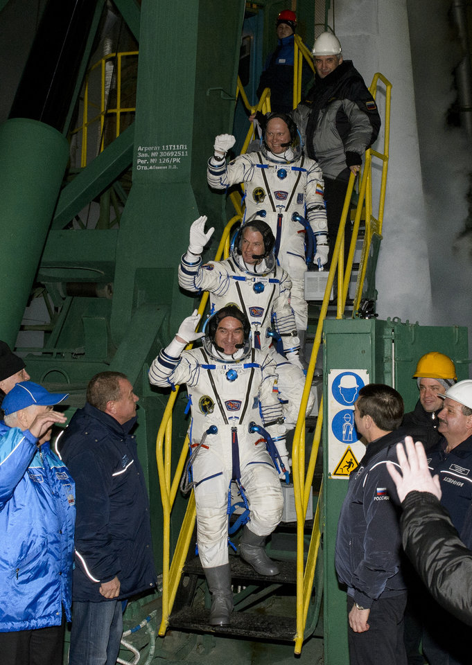 Photo - Expedition 39 Soyuz commander Aleksander Skvortsov, of the Russian Federal Space Agency (Roscosmos), followed by, flight engineer Steve Swanson of NASA, middle, and flight engineer Oleg Artemyev of Roscosmos, wave farewell prior to boarding the Soyuz rocket for launch from the Baikonur Cosmodrome Wednesday, March 26, 2014, in Baikonur, Kazakhstan. (AP Photo/NASA, Joel Kowsky) MANDATORY CREDIT