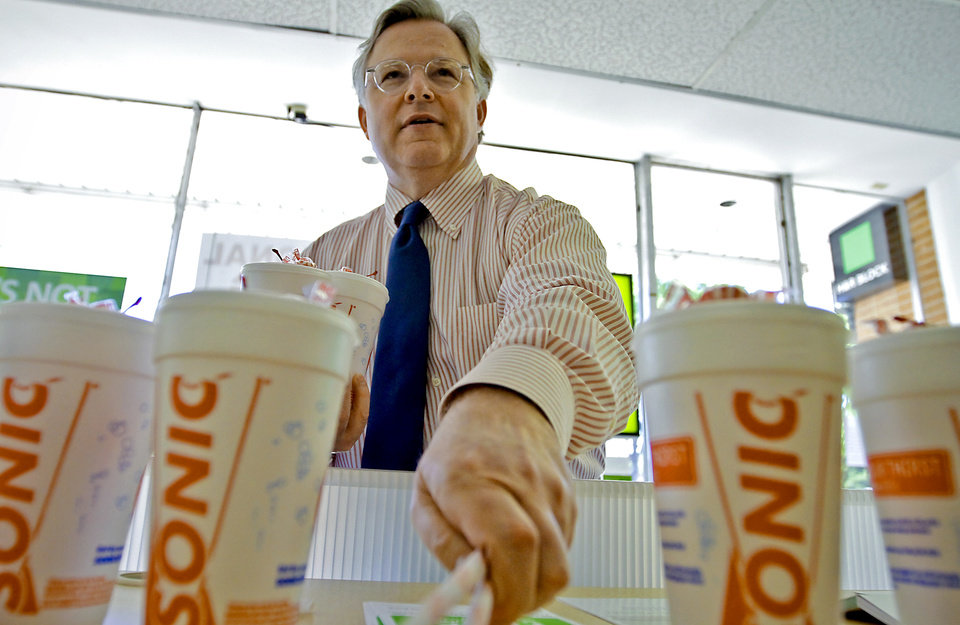 Photo - Sonic CEO Cliff Hudson grabs some straws as he delivers drinks to workers and patrons of the H&R Block near 23rd Street and Walker Ave.  on Tuesday, April 17, 2012, in Oklahoma City, Oklahoma.  Photo by Chris Landsberger, The Oklahoman