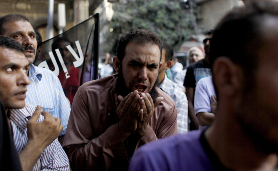 Photo -   CORRECTS NATIONALITY OF FILMMAKER - An Egyptian man chants slogans during a demonstration in front of the U.S. embassy in Cairo, Egypt, Wednesday, Sept. 12, 2012, as part of widespread anger across the Muslim world about a film ridiculing Islam's Prophet Muhammad. A man identifying himself as Sam Bacile, a 56-year-old California real estate developer, said he wrote, produced and directed the movie. He told the AP he was an Israeli Jew and an American citizen. But Israeli officials said they had not heard of Bacile and there was no record of him being a citizen. (AP Photo/Nasser Nasser)