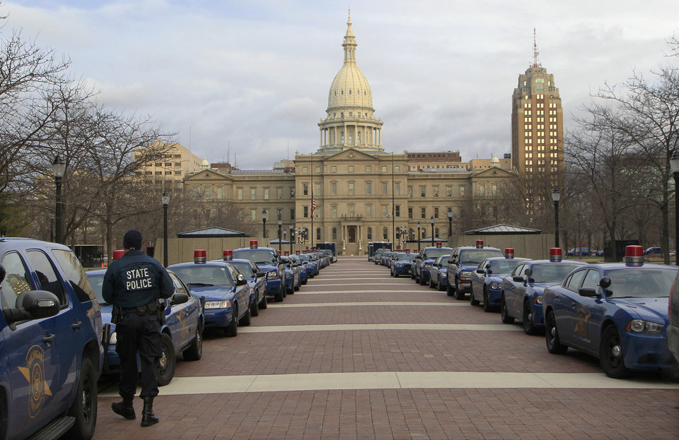 Photo - Michigan State Police cruisers line the pedestrian walkway west of the state Capitol in Lansing, Mich., Monday, Dec. 10, 2012. Lansing authorities were bracing for an onslaught of protesters Tuesday. They increased police presence and planned road closings and parking restrictions around the Capitol for the planned protests against the Michigan legislature's right-to-work proposals which passed last week. (AP Photo/Carlos Osorio)