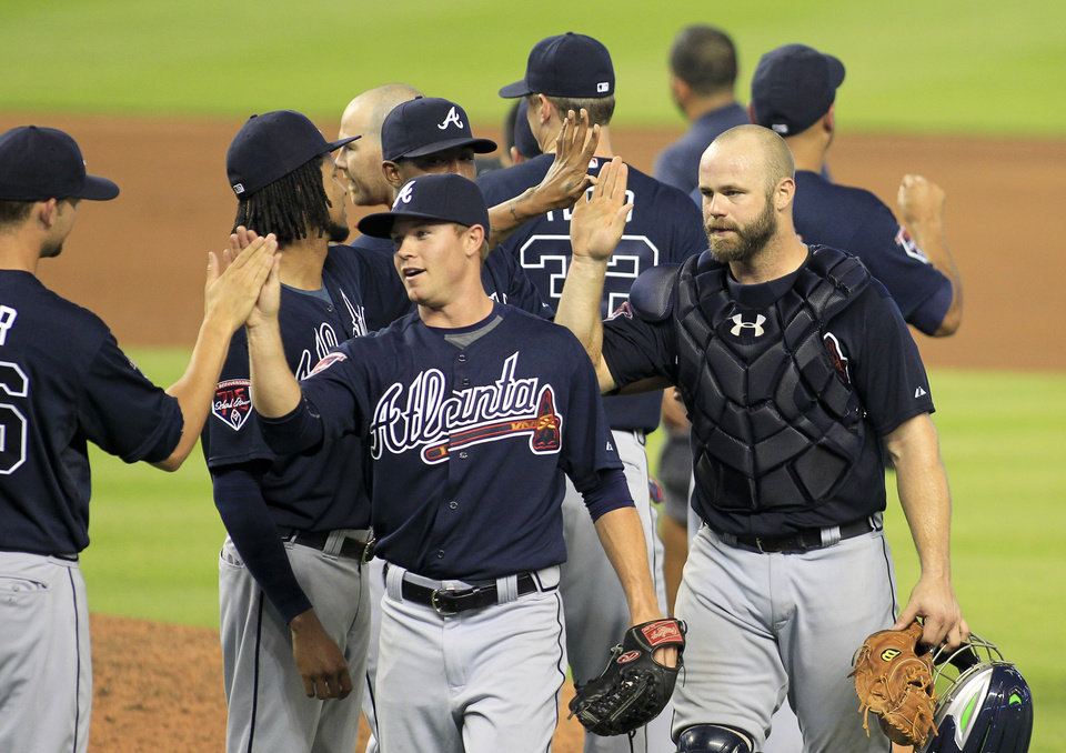 Photo - Atlanta Braves catcher Evan Gattis, right, and relief pitcher Shae Simmons, center, celebrate with teammates after defeating the Miami Marlins 4-2 in their baseball game in Miami, Sunday, June 1, 2014. (AP Photo/Joe Skipper)