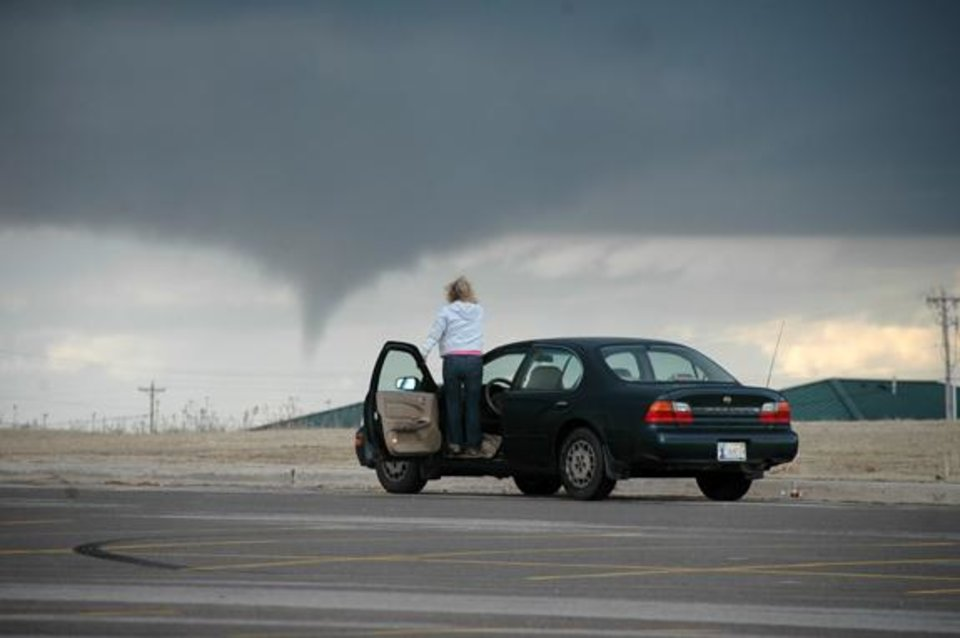 Photo - A women gets a step higher on her car in Elk City to get a better view of a tornado just minutes after it began to form and shortly before it hit the town of Hammon. Around 5:30 p.m., many people had come out to see the storm as this woman did. Submitted by Matt Meason Elk City Daily News.