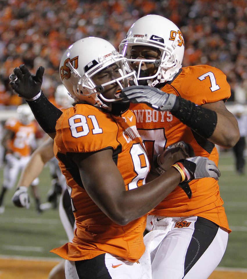 Photo - Oklahoma State's Justin Blackmon (81) and Michael Harrison (7) celebrate Blackmon's touchdown during the Bedlam college football game between the University of Oklahoma Sooners (OU) and the Oklahoma State University Cowboys (OSU) at Boone Pickens Stadium in Stillwater, Okla., Saturday, Nov. 27, 2010. Photo by Chris Landsberger, The Oklahoman
