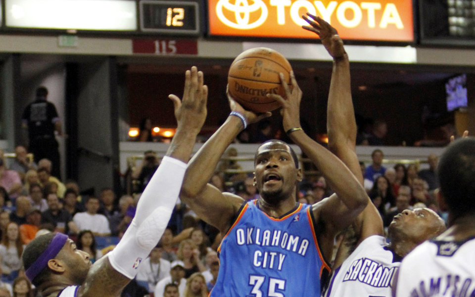 Oklahoma City Thunder forward Kevin Durant (35) shoots between Sacramento Kings' DeMarcus Cousins (15) and Travis Outlaw during the first quarter of an NBA basketball game in Sacramento, Calif., Friday, April 20, 2012. (AP Photo/Rich Pedroncelli) ORG XMIT: SCA103