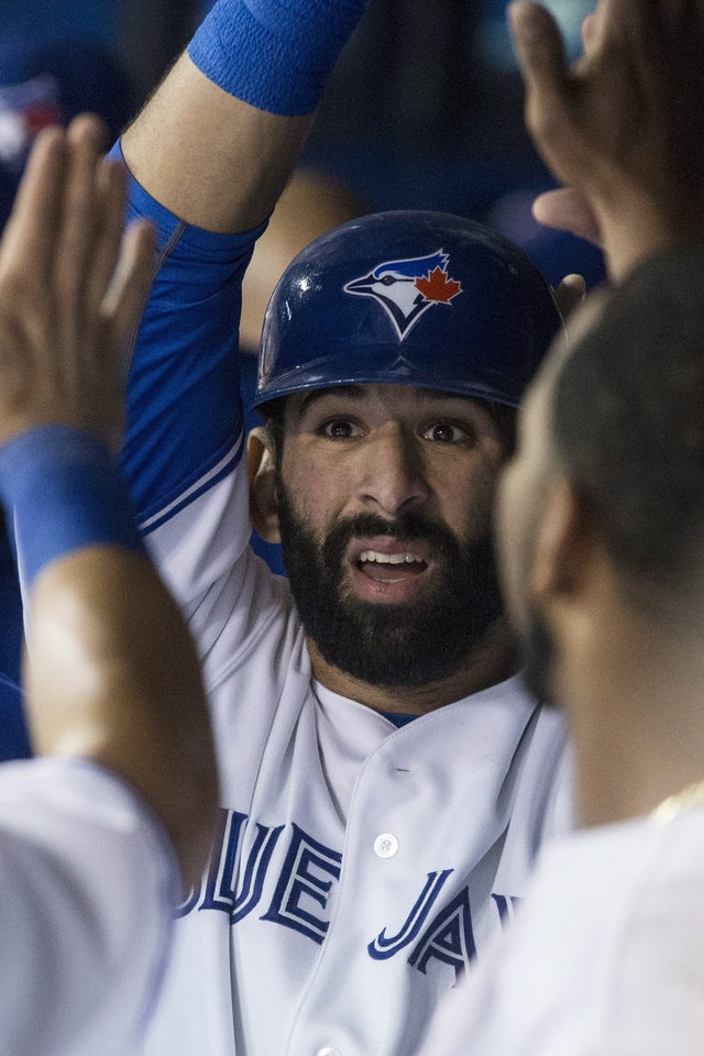 Photo - Toronto Blue Jays' Jose Bautista celebrates in the dugout after scoring on a hit by Adam Lind against the Houston Astros during the first inning of a baseball game Wednesday, April 9, 2014, in Toronto. (AP Photo/The Canadian Press, Chris Young)