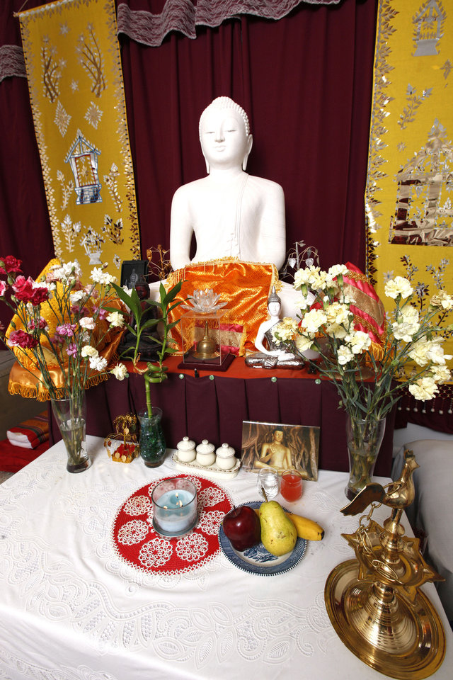 Photo - A Buddha statue is featured prominently on the altar area at the Oklahoma Buddhist Center in south Oklahoma City. Photo by Paul B. Southerland, The Oklahoman   PAUL B. SOUTHERLAND - PAUL B. SOUTHERLAND
