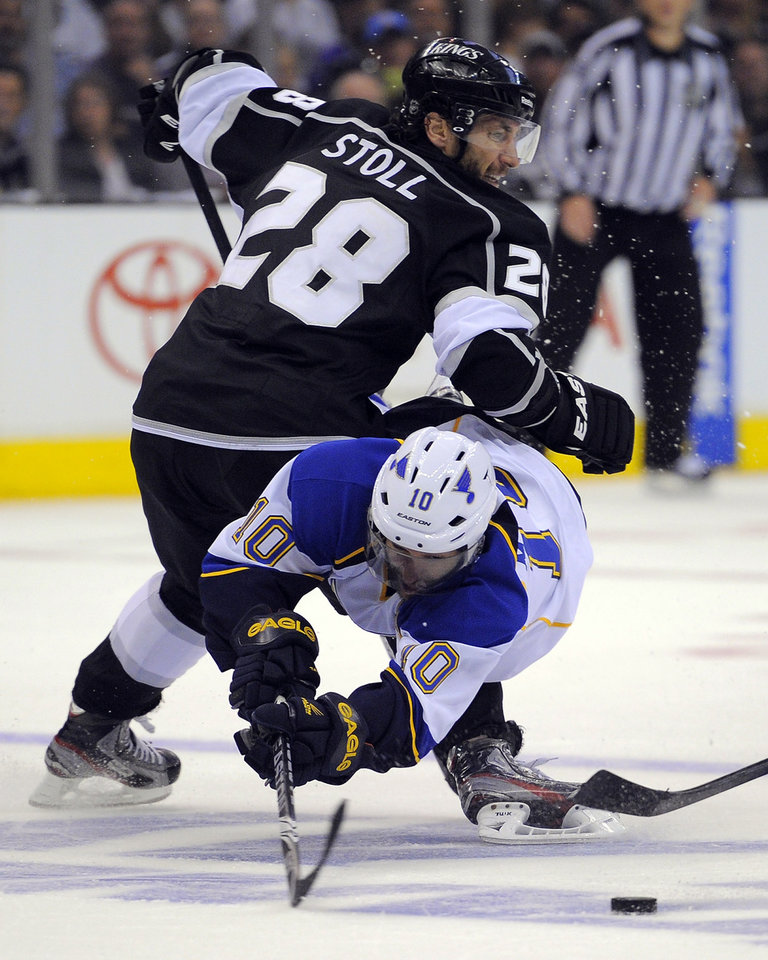 Photo -   St. Louis Blues center Andy McDonald, below, trips over Los Angeles Kings center Jarret Stoll as he tries to pass the puck during the third period in Game 4 of an NHL hockey Stanley Cup second-round playoff series, Sunday, May 6, 2012, in Los Angeles. The Kings won 3-1 to win the series 4-0. (AP Photo/Mark J. Terrill)